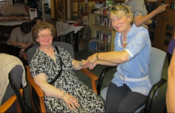 Claire Hafner giving Angela Pickford a hand massage
